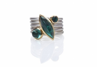 Three indicolite tourmalines set in 18ct gold on frosted silver bands with two blank spacer rings.