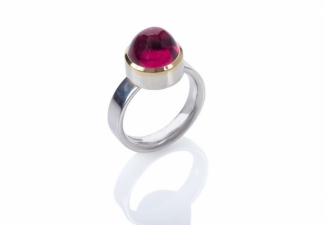 A rubellite tourmaline cabochon set in 18ct gold on a polished band.