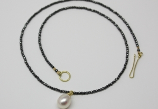 Shiny black hematites with a large lustrous freshwater pearl drop. 18ct yellow gold clasp and pendant fitting. 43-5 cms.