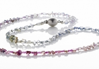 A rainbow of natural rough cut sapphires with faceted natural sapphires between and a silver ball clasp
