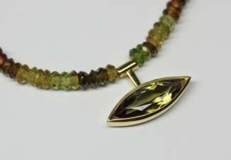 Necklaces - Green/brown faceted tourmalines with a faceted Andalusite marquise pendant. Clasp and pendant 18ct gold. 43/44cms.