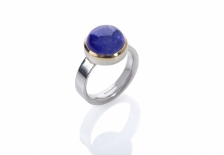 A Tanzanite cabochon set in 18ct gold on a polished band.