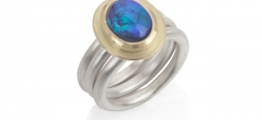 A stunning oval shaped black opal set in 18ct gold on frosted silver rings.