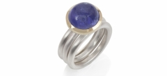 A tanzanite cabochon set in 18ct gold on frosted silver rings.