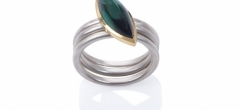 A marquise shaped, indicolite tourmaline cabochon set in 18ct gold on a frosted silver band. Shown with two optional spacer rings.
