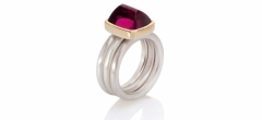 A loaf shaped rubellite tourmaline set in 18ct yellow gold on three matte silver rings.
