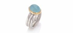 An oval aquamarine cabochon set in 18ct yellow on three matte silver rings.