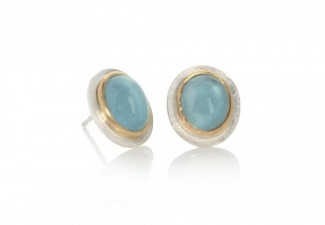 Oval aquamarine cabochon studs set in 18ct gold on textured matt silver